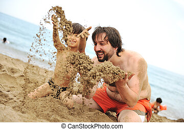 Playing together in sand on beach, young father and a little son