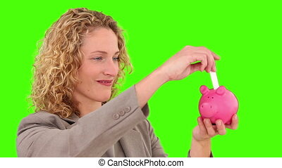 Curly-haired woman saving up money in a piggy bank -...