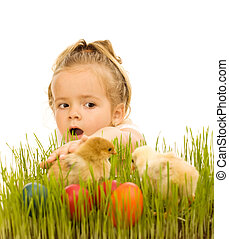 Little girl catching the easter chickens in the grass
