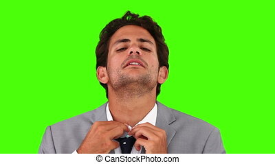 Young business man putting on his tie against a green screen