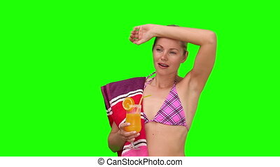 Woman in swimsuit sipping a cocktail because she is feeling too hot
