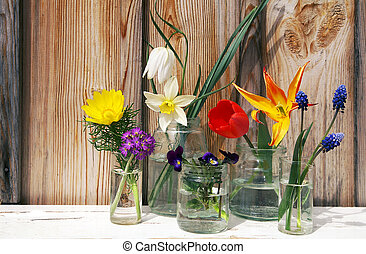 Spring flowers display on wood background - A display of...