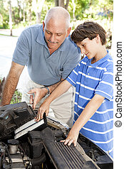 Boy Helps Dad - Boy helping his father change the air filter...