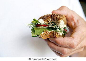Bitten healthy sandwich on a man's hand