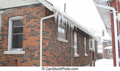 Winter house. - Snow falls and icicles hang from a suburban...