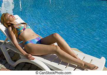 woman tans in chaise lounge at pool