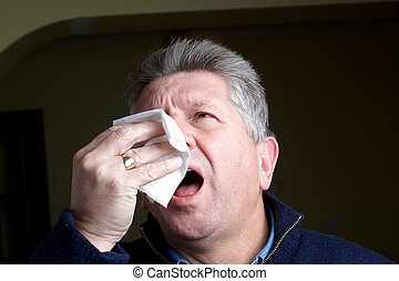 Mature man with  a cold sneezing