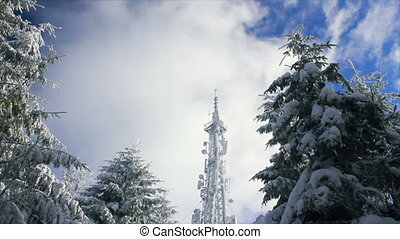 Cellular tower in snow on a blue sky background with clouds...
