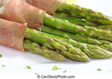 Green asparagus with ham (Selective Focus, Focus on the two asparagus heads in the front)