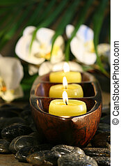 Spa setting with pebbles, candles and flowers