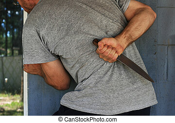 man hides knife - cropped image of a man with a knife behind...