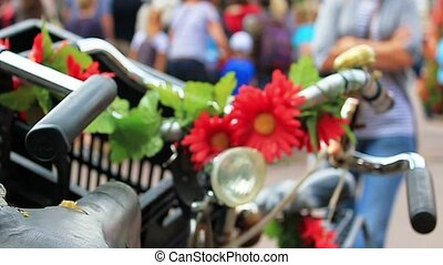 bikes and flowers - two traditional bycicles parked on a...