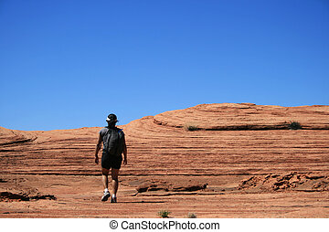 slickrock hiker - a woman walks across sandstone slickrock...