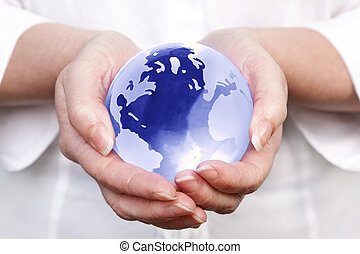 World in your hands - Photo of a woman holding a glass globe...