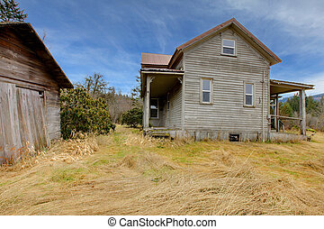 Very old grey house and shed on the farm land - 110 years...