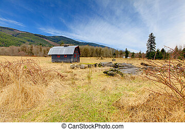 Cute grey and red rustic old barn in the fieild - Build in...