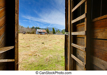 View from inside of the barn to the farm land with shed and...