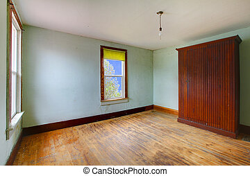 A very old empty room with large closet and blue walls -...