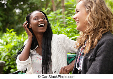 Cheerful women enjoying chat in the park - Close-up of two...
