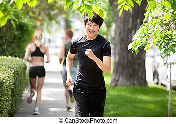 People jogging in the park - Portrait of a man running...