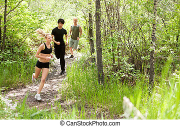 Friends running in the forest - Three friends running in the...
