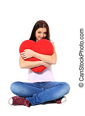 Attractive teenage girl hugging red heart-shaped pillow. All...
