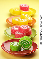 Colorful candy in multicolored saucers on yellow background.
