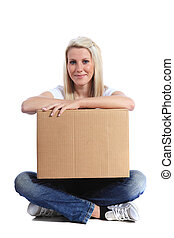 Carrying a moving box - Attractive young woman sitting on...