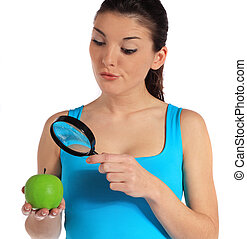 Food inspection - Attractive young woman checking an apple...