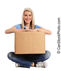 Moving box - Attractive young woman sitting on floor holding...