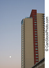 Red and White Condo Tower Under Full Moon at Dawn