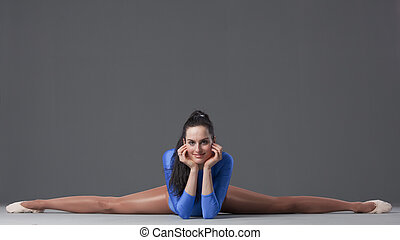 splits - smiling female gymnast in splits pose on the ground