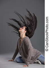dancing woman swinging hair over grey background