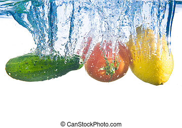 Fruits fell into the water. Close-up. Isolated on white.