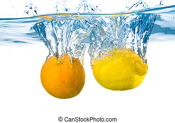 Lemon and orange fell into the water. Close-up - Lemon and...