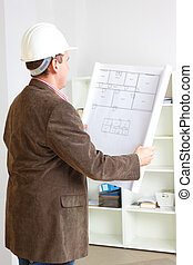 Architect working with plan - Architect looking at home...