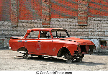 Broken-down car - A broken-down red car without wheels