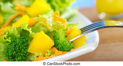Fresh and light broccoli-mango-carrot salad on white plate with a piece of mango on fork and a glass of orange juice dressing in the background (Very Shallow Depth of Field, Focus on the mango and bro