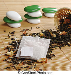 Teabag with empty white label on lose green tea with dried...