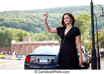 Woman Hailing a Taxi Cab - A beautiful brunette woman waving...