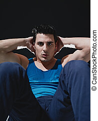 man doing series of sit-ups on black background - young...