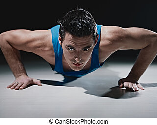 Man doing push-ups on black background - Young caucasian...