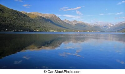 mirrored tranquility - still water reflecting a mountain in...