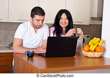 Happy couple with coffee and laptop