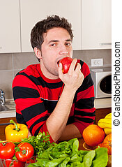 Young man eating apple in kitchen
