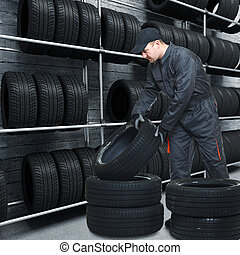 mechanic on duty - caucasian mechanic at work with tires and...