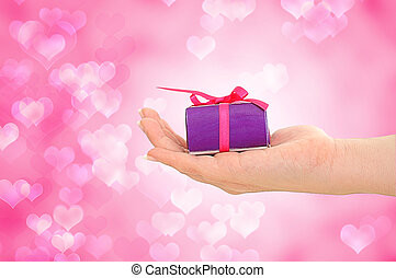 Female hand holding purple gift on pink heart background