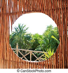 circle window in wooden sticks cabin tropical Jungle -...