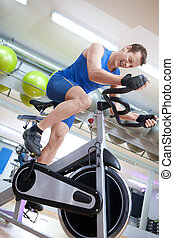 Man cycling on spinning bike with g - Cycling fit man on...