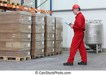 worker checking stocks - A worker checking stocks in a...